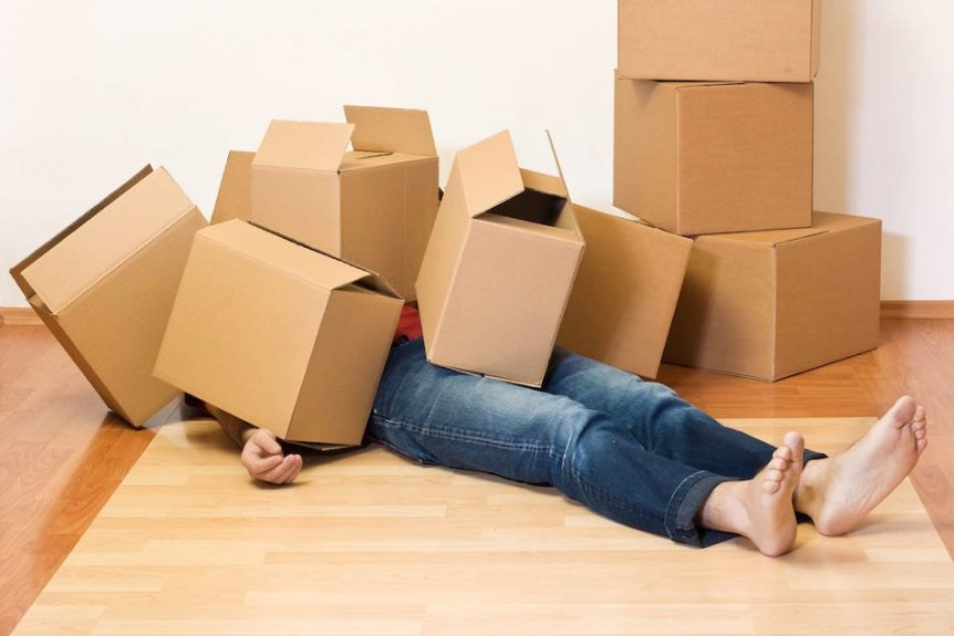 person under moving boxes